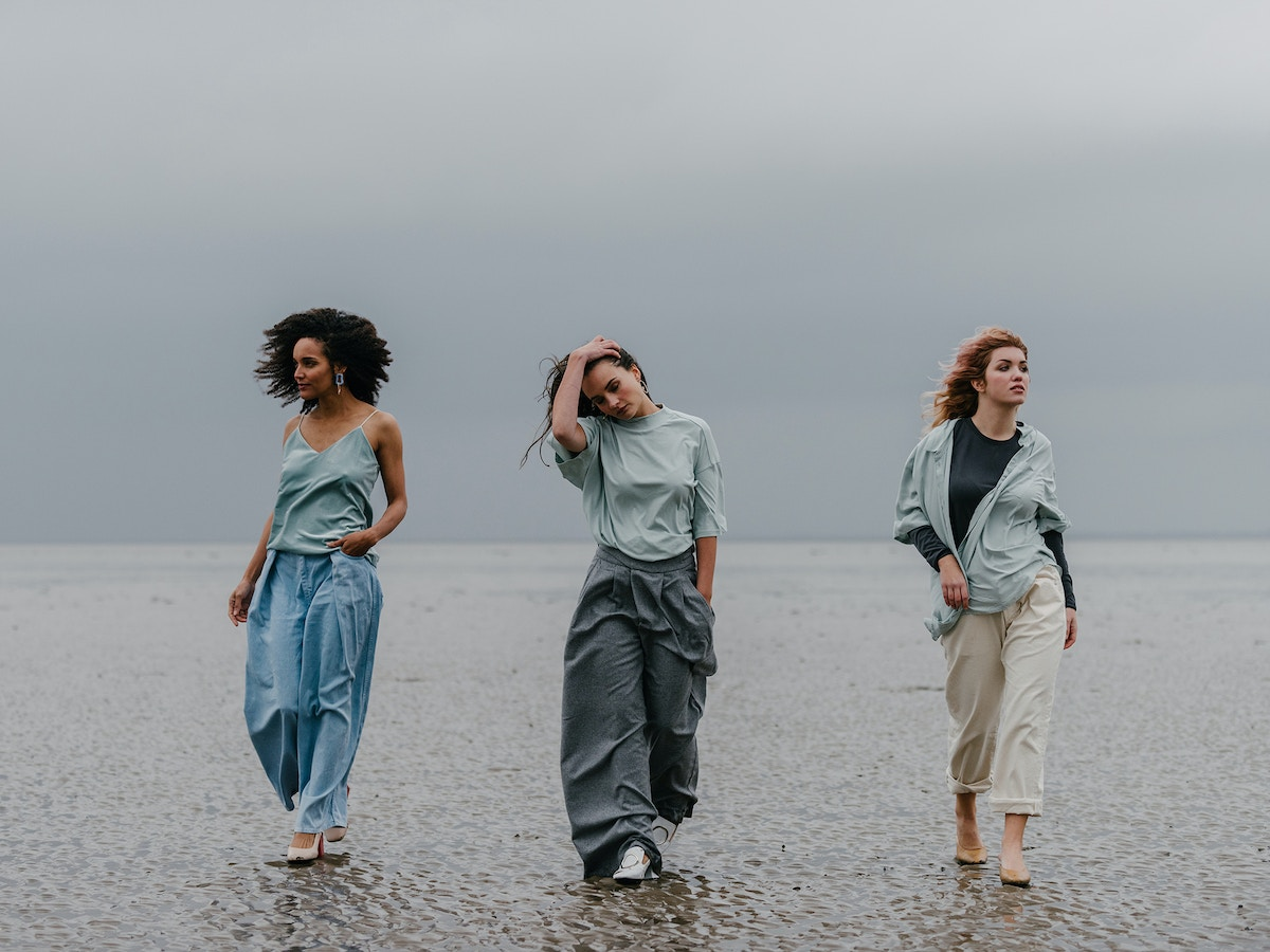 Three women walking along a beach towards the camera. The woman in the middle has her right hand on her head. They are all wearing shades of blue.
