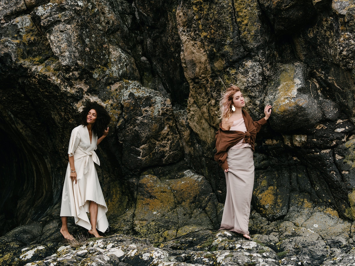 Two women standing barefoot on a cliff face.