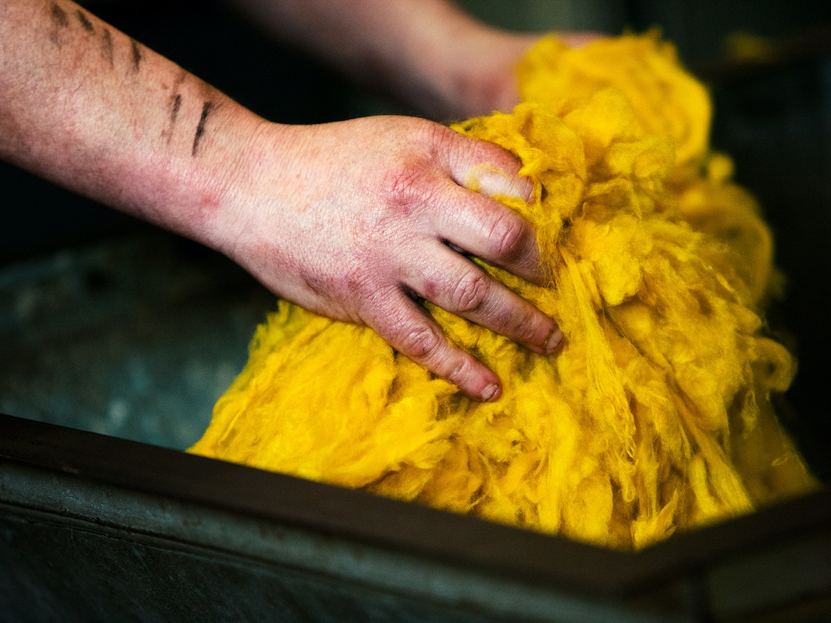 Two hands grasping onto a bright yellow bundle of cashmere.