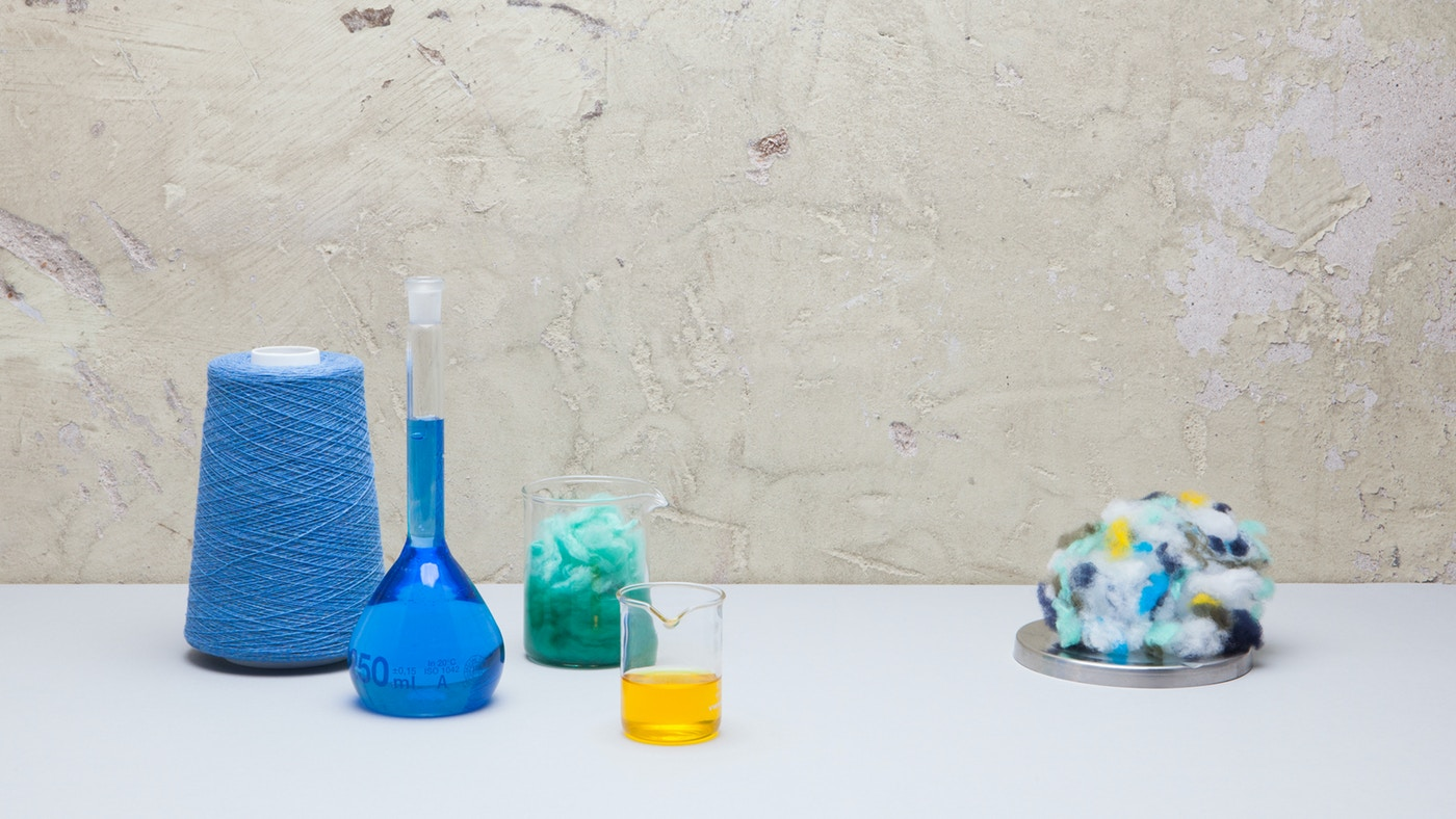 A loom, bottle with blue liquid, glass with yellow liquid and a ball of multicoloured fabric sitting on a white tabletop.