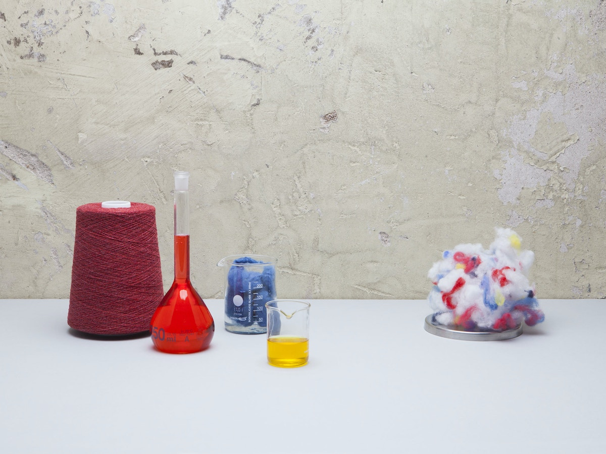 A loom, bottle with red liquid, glass with yellow liquid and a ball of multicoloured fabric sitting on a white tabletop.